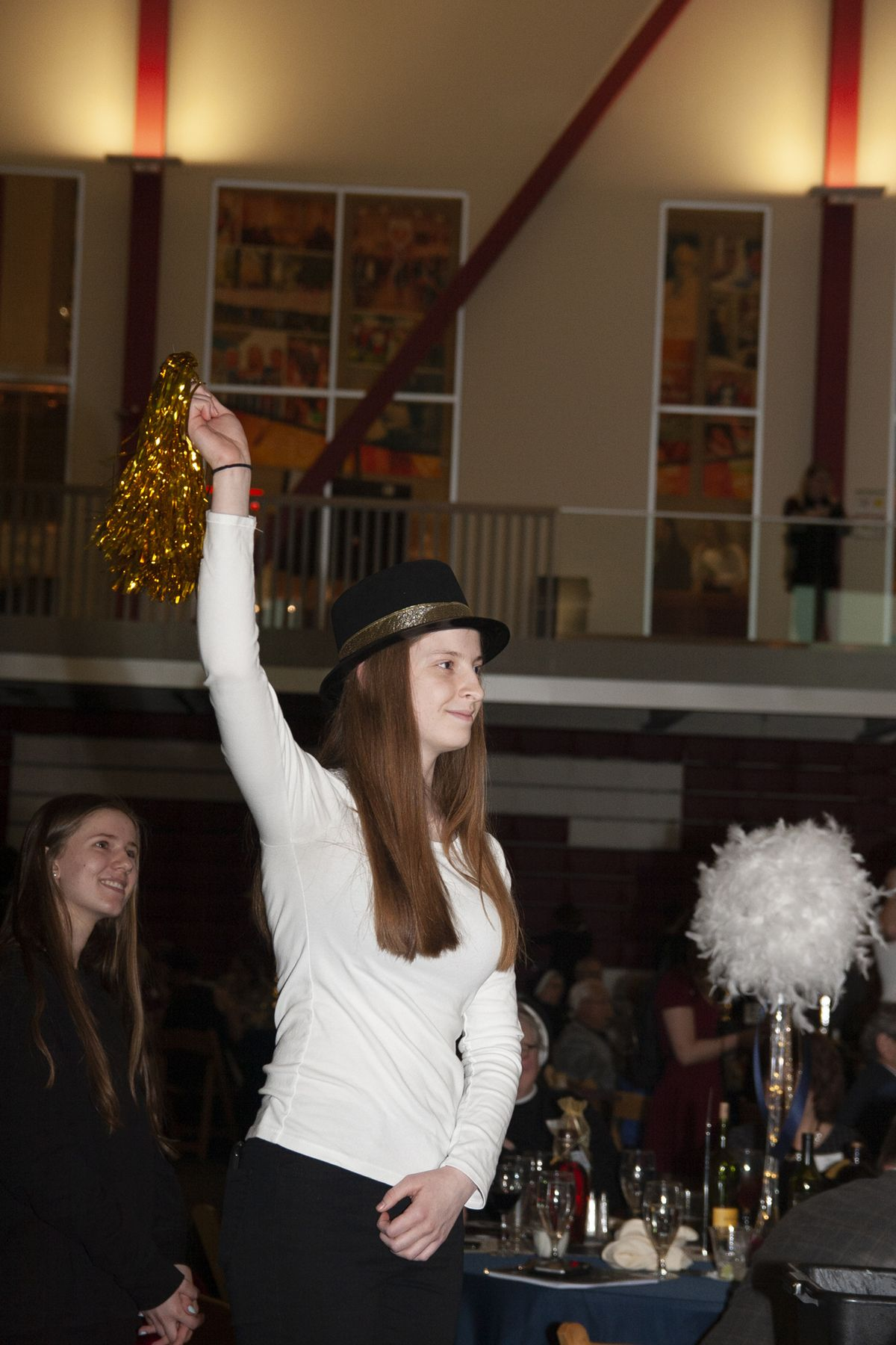 A CJ student raises her pom to indicate a new bid on an item