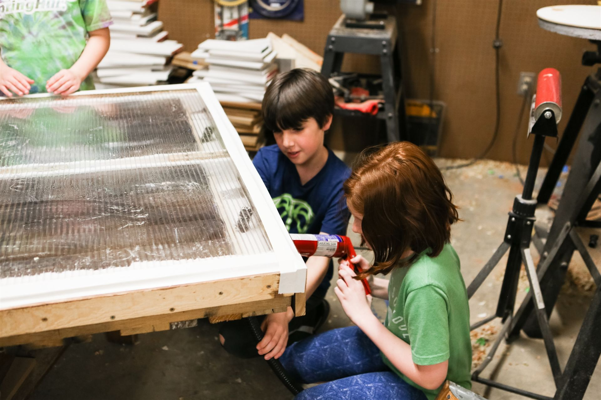 In STEM class, students often do engineering projects that tie in with their other classes. Last year, the students built a SOLAR HEATER in our wood shop to warm the Orchard hoop house in the winter. Students painted soda cans black and arranged them in a plexiglass covered frame, which they attached using recycled vacuum tubes to the hoop house.