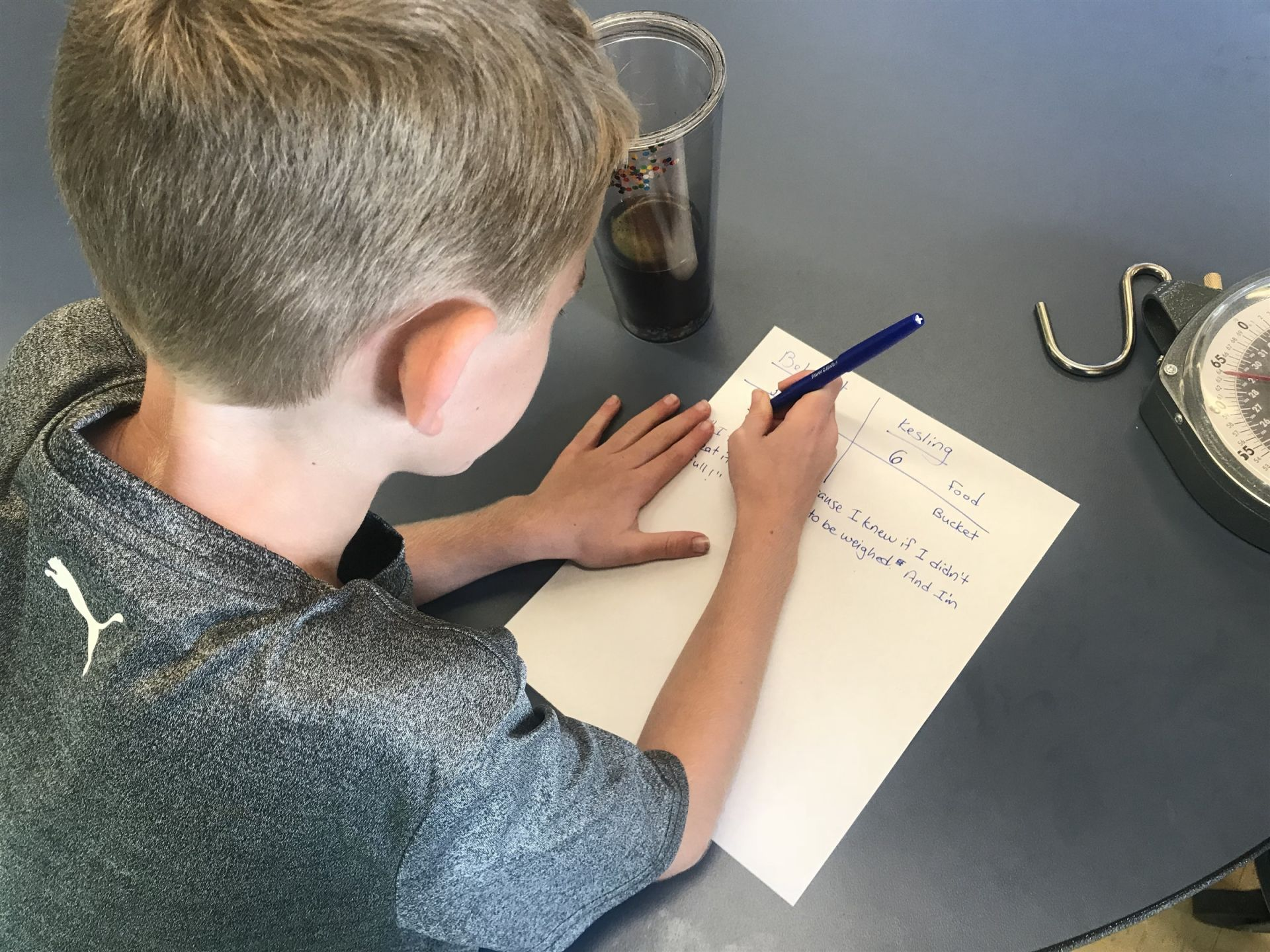Literacy; Writing; Science: Serious work doesn't only happen in the classroom.  When your project work involves using real tools to quantify food waste, you might as well take the opportunity to record your predictions and thoughts right at the cafeteria table! In this photo, a second grader jots down notes to help him remember what to share back with his classmates when finishing weighing the food waste bucket that day.