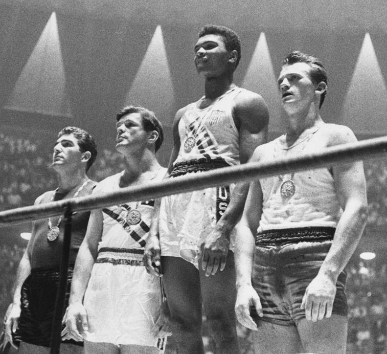 Cassius Clay, Jr., who later took the name Muhammad Ali, is shown here after he won a gold medal at the Olympics in 1960. He was born on January 17, 1942, in Louisville, Kentucky. He was an American professional boxer, who started at the age of 12 when someone stole his bike. A Louisville policeman told him he should take up boxing. At first, Clay wasn't very good at boxing but he won his first match in 1954, six weeks after he started. Clay's dad was so impressed by his son that he predicted he would be world champion one day.   In 1960, Clay won a spot at the Summer Olympics in Rome, almost deciding not to go because he was afraid of flying in airplanes. He wore a parachute the entire time he was in the air. At the Olympic Village, Clay engaged with athletes from all over the world and was more well known for being nice than being good at boxing. He surprised many by winning a gold medal against Polish boxer Zbigniew Pietrzykowski.    After the Olympics, Clay decided to turn professional, vowing to win the heavyweight championship of the world. In 1961, Clay went up against a fighter named Gorgeous George, learning that the more he talked, the more people watched him fight. He also became increasingly political, converting to the Nation of Islam and, in 1964, taking the name Muhammad Ali.