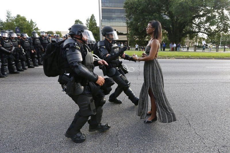The woman in this picture is being arrested for breaking a police line at a protest. The police said that if you cross this line you will be arrested. This photo is taken in Baton Rouge. Iesha is the woman in the photo. She was arrested and detained by authorities. The protest began in the aftermath of the shooting by police of Alton Sterling and Philando Castile. She did this because she wanted to take a stand to the police and promote the Black Lives Matter movement.   Patrisse Khan-Cullors, Alicia Garza, and Opal Tometi are the co-founders of the Black Lives Matter movement. They started Black Lives Matter because Trayvon Martin was wrongly killed, and he was African American so, on Facebook Alicia posted that she loves black people and that they matter. Patrisse responded and made the quote #blacklivesmatter, then Opal agreed with it, and they all started working at Black Lives Matter. Black Lives Matter is about finding equal rights and to help stop police brutality and racism. The Black Lives Matter movement is also about stopping shootings that are unnecessary. To help with the Black Lives Matter movement there are many protests in response to racism. The protests are mainly against police brutality because that is where most aggressive racism occurs.   Black Lives Matters is also about building power to intervene in any violence that occurs in black communities. Many African Americans are part of the protests to fight for their lives.