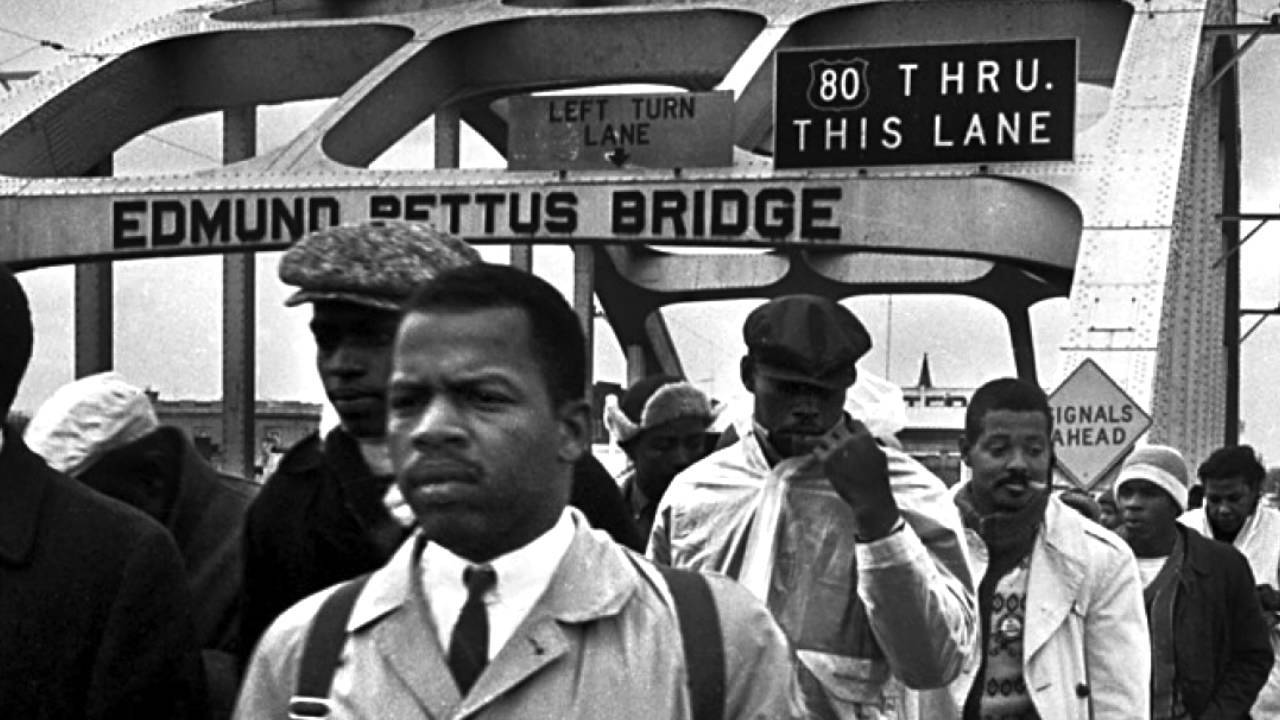 John Lewis is currently a U.S. Representative from Georgia and has been serving in Congress since 1987. As a civil rights activist, Mr. Lewis was very active in a host of civil rights events during the 1960's. Pictured here he, along with Hosea Williams, is leading a group of marchers across the Edmund Bettus Bridge in Selma, Alabama on March 7, 1965.   The bridge over the Alabama river is named after a confederate brigadier general and grand dragon in the KKK. It served as the flashpoint for what became known as Bloody Sunday.   The Selma marches were to increase voter registration and raise national awareness of the effects of segregation policies in the south. The marches were being thwarted by the Alabama authorities.   Soon after this photo was taken, the marchers were ordered to disperse, but instead began to hold a group prayer on the far side of the bridge. They were tear gassed and attacked with night sticks. Mr. Lewis suffered a fractured skull during the event and the crowd retreated to a nearby church. Before being taken to the hospital, Mr. Lewis made a televised address calling for President Lyndon Johnson to intervene in what was happening in Alabama.