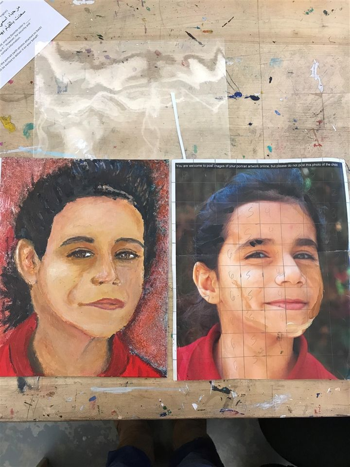 Rana (photographed, R), a 7 year old Syrian refugee child is painted (painted, L) by Lera Davis, DSHA '20.