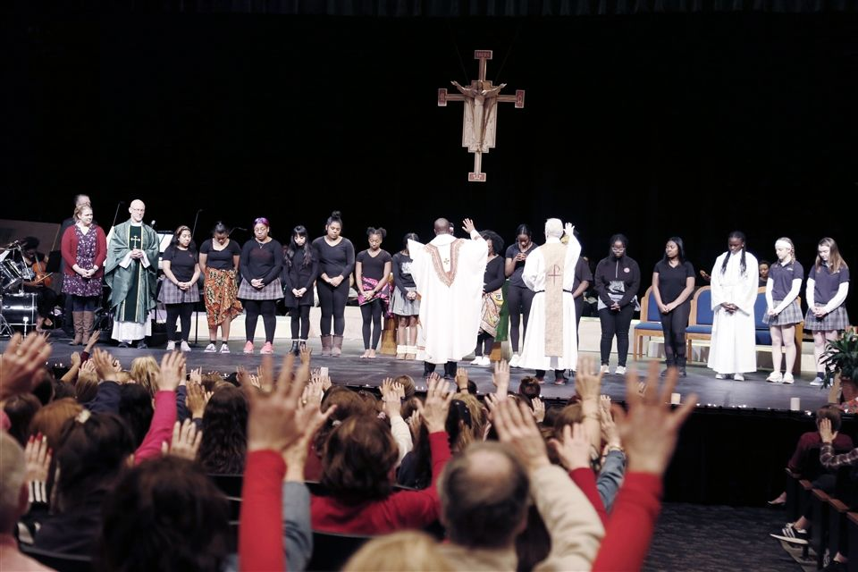 Raised hands from the school community join Fr. Peter Patrick Kimani and Fr. Dennis Thiessen, SDS, in blessing the participants of the Civil Rights Pilgrimage, which was to take place this summer. The pilgrimage was cancelled due to COVID-19.