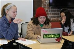 Three students in class working on a small group project with a laptop.
