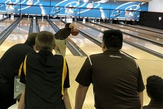 CJ Davy '19 bowls the tenth frame of the last game, as Matthew Martinez '19 observes.