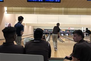 Kolton Hall '21 bowls in the fifth game, as the team observes.