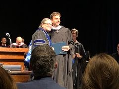 Mr. Reynolds accepting his diploma from the President of Middlebury College, Laurie L. Patton.