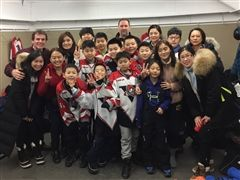 The Flying Bears, their parents and hosts in the locker room at the Pat Burns Arena.