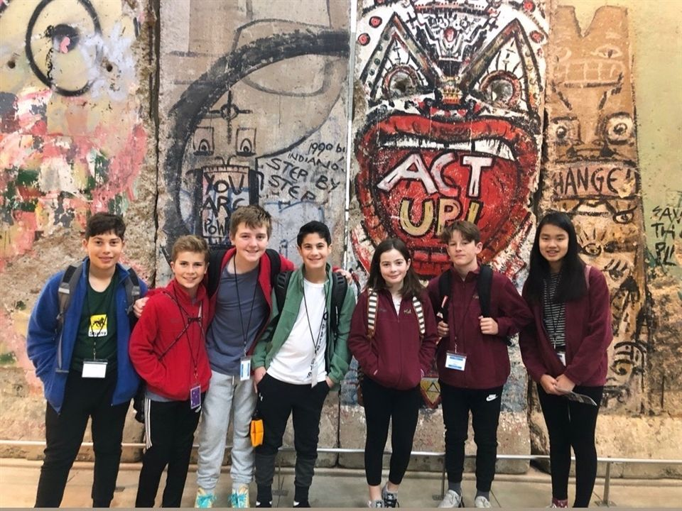 CS students in front of a piece of the Berlin Wall at the Newseum