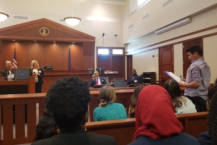 Jury foreman Ameen Altalib (7th Grade) delivering his jury's verdict as the judge, attorneys, and a crowded courtroom of spectators listen.