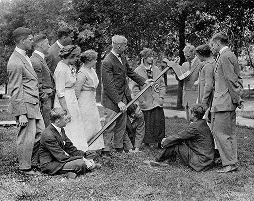 An archival photo from the 1920s shows students posing with the axe.