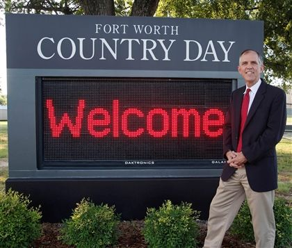 Head of School Eric Lombardi standing in front of a Welcome sign.