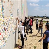 "Visitors to the Path to Peace project at the Israel-Gaza boarder help create a mosaic that says ""Peace"" in Hebrew, Arabic, and English."