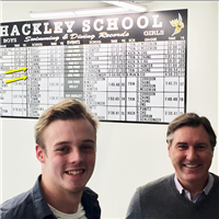 Aidan Wilson '20 and Bruce Dunbar '85 in front of the records board.