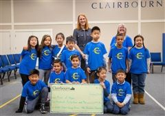 Clairbourn's second-grade class presents Door of Hope Executive Director, Rev. Magan Katerjian, with a check for $1044.96 at the school's Morning Assembly.
