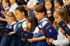 First-graders sing hymns from the Morning Assembly Handbook.