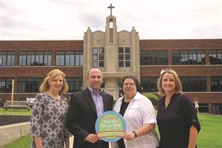 Vicky Adams, Elementary School Principal, Kevin Smith, Head of Schools, SIster Julia Sub-Prioress and Janou Farrell accept the Tulsa Kids Family Favorite Award.