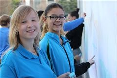 2 Middle School girls standing in front of a chalk wall. One is wearing a blue school polo, the other is wearing a lightweight school jacket