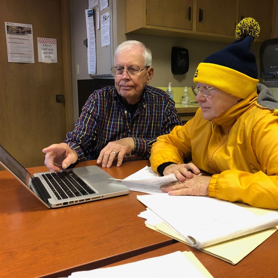 John Dietz '54 (left) helps a client search for affordable housing.