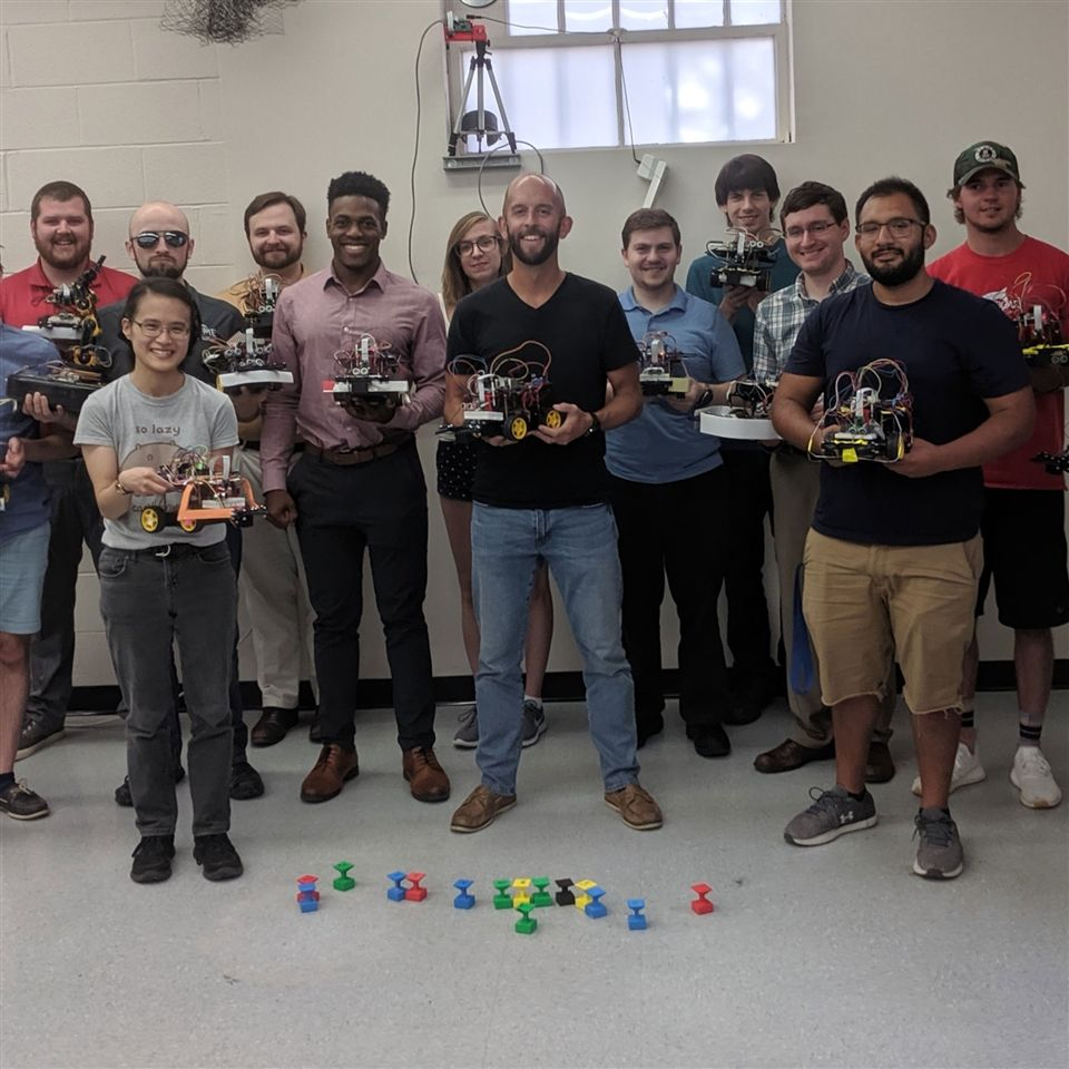 Steve Mitchell '01 (center) and his Autonomous Robotics class at UMD hold their four-wheeled ground robots.