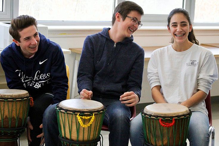 3 students laughing while playing the drums