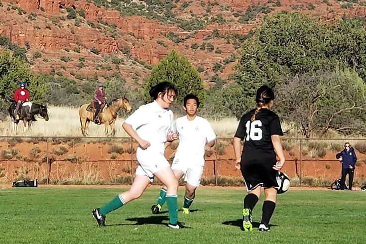 Soccer team playing with mountains in background