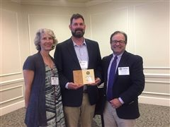 Collegiate's Institute for Responsible Citizenship Special Programs Manager Anne Rusbuldt, Middle and Upper School STEAM Coordinator Dan Bartels and Collegiate parent and community mentor Bo Fairlamb accept the Connect the Dots Curriculum Award.