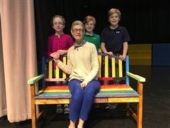 Retired 1st Grade teacher Sallie Tinney with students and a Buddy Bench