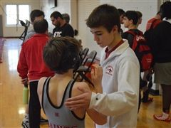 Luke Hart '21 (right) encourages 8th grader Jack Parker before his match.
