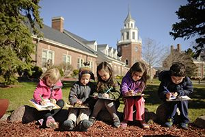 Lower School students writing outside in front of USM tower.