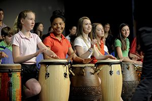 Middle School students smiling while playing African drums.