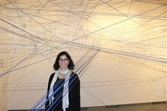 Artist-in-residence Kim Schoenstadt stands among the string following the completion of her interdisciplinary project with Crossroads students at Sam Francis Gallery.