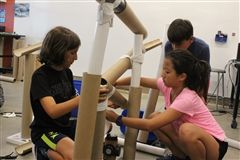 Students in the Summer at Crossroads engineering class use household items during a team-based challenge July 10.