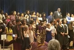 Students join the founder of the Virginia Black History Month Association on stage during their annual gala.