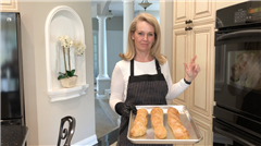Nathalie Mould P'22 displays freshly baked baguette.