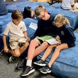 A sixth grader reads to two third grade students.