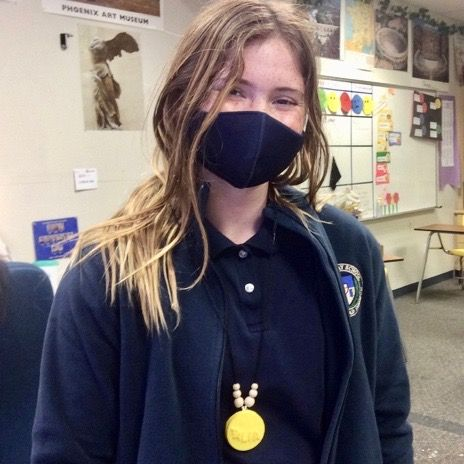 Sixth grade student wears her bullae (necklace) in class