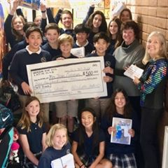 Latin Club presents a $500 check for Mbahe.