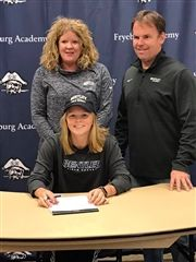 On National Signing Day, Wednesday, November 13,  Abigail Hewes '20, signs her contract to play Division II field hockey with Bentley University. Her parents, Kirsten and Harry Hewes, stand in the background.