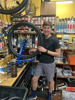 Benjamin Kampine '24 continues to repair bikes during an apprenticeship; Benjamin will use the skill he's learned to give refurbished bikes to other children.