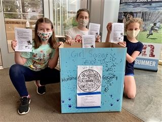 Girl Scout Troop 40 members Sophia Hill '28, May Cox '28, and Charlotte Soslow '28 show off the pamphlets and collection box where students can drop off donations for the Nashville Humane Society.