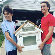 Oscar Fox '21 and Stefan Pretorius '21 carry the Little Free Library, to be installed Monday, April 22.