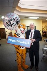 Peabody the Tiger joins Director Vince Durnan during the Tiger Give Back Challenge in March.