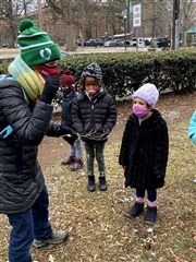 LS Naturalist Teacher Lauren Hagan, Abner King '33, Zoë Mathis '33, and Stella Luecke '33 observe a twig from the tree on campus adopted by Red Door kindergarten.