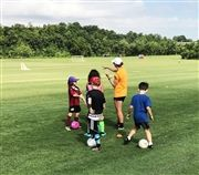 HS Girls Soccer Head Coach & PE Teacher Megan Masuhr instructs students during a soccer clinic in 2019.