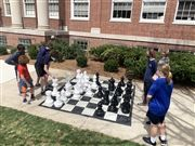 MS Chess students take a break from virtual play to practice outside on a sunny day using a lifesize board.