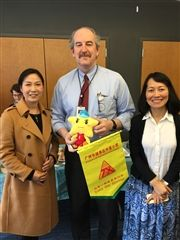 Director Vince Durnan and Trustee Xiu Cravens accept gifts from principals visiting from China.