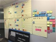 The USNA office wall is filled with sticky notes to organize the 2019 Evening Classes schedule.