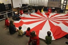 Upper and Lower School students play a parachute game together.